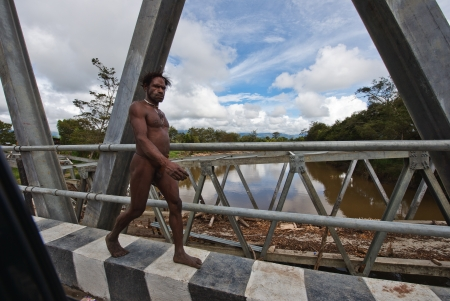 WAMENA, PAPUA, INDONESIA - JUNE, 20:The naked Papuan man goes on the asphalted road on June, 20, 2012 near Wamena, Papua, Indonesia.