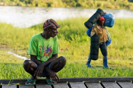 transfers:  NEW GUINEA, INDONESIA - JUNE 26: The local Papuan man  observes as the porter transfers baggage. On June 26, 2012 in  Unknown Village, New Guinea, Indonesia  Editorial
