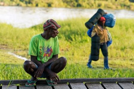 traslados: Nueva Guinea, Indonesia - 26 de junio: El hombre pap� locales observa como el bagaje transferencias porter. El 26 de junio de 2012 en Desconocido Village, Nueva Guinea, Indonesia Editorial