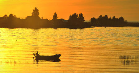 The boat with the fisherman at sunset photo