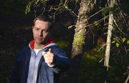 demotion: In the Wood  young man points a finger at you Stock Photo