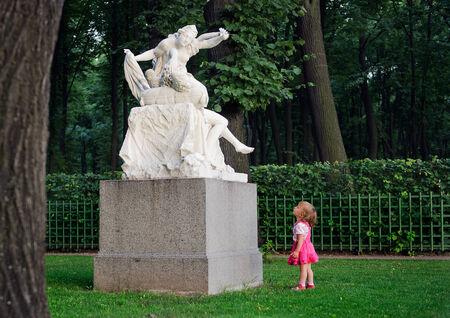 """psique: La ni�a con asombro se ve en una escultura de """"Cupido y Psique"""" en el parque """"Jard�n de verano"""" de edad en San Petersburgo, Rusia"""