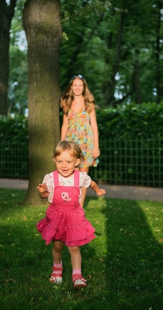 face of infant: The smiling little girl run on the green lawn in the park with mother on the background.