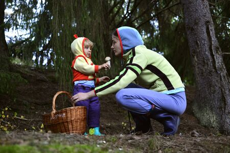 A mother and her little girl picking mushrooms in the forest in the bascket, showing  ones photo