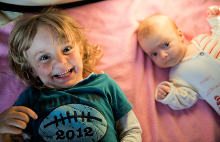 Cute newborn baby and his beautiful toddler sister together on a pink bed. Two children lie on a bed. Portrait photo