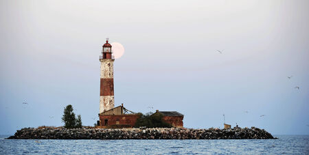 warning lights: Moon and Old lighthouse of the Suho  island in Ladoga.