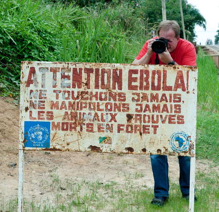 visitors area: MAKOUA, CONGO, AFRICA - SEPTEMBER 27: Journalist and  sign warns visitors that area is a Ebola infected. Signage informing visitors that it is a ebola infected area. September 27, 2013,Congo, Africa.