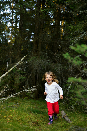playtime: Smiling Happy little girl running on the summer forest