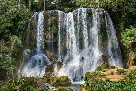 Waterfall in a lush rainforest. Beautiful waterfalls or cascades in El Nicho, El Nicho waterfall, in Scambray mountains. Cienfuegos province, Cuba. Stock Photo