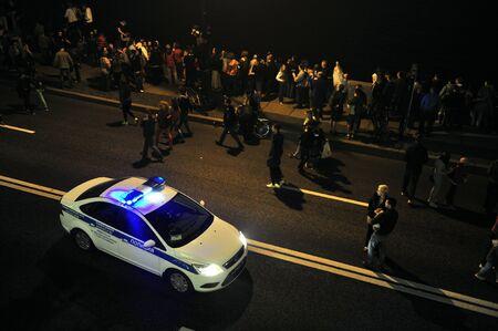 festivities: ST.PETERSBURG, RUSSIA - JUNE 24: The police car patrols Neva River Embankment during festivities in June. Celebration Scarlet Sails show. White Nights Festival, June 24, 2015, St. Petersburg, Russia Editorial