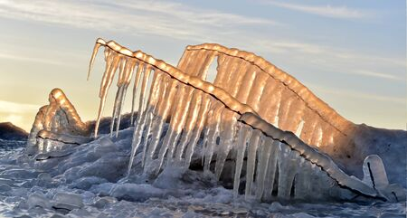 thawing: Abstract frozen thawing icicles with sun in background, caramel color. Winter Sunset light Stock Photo