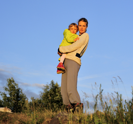 solar flare: Young Attractive young mother holding a little girl in her arms at sunset light.  Walk in the autumn warm evening outdoors at sunset. Solar flare lights Woman and child.