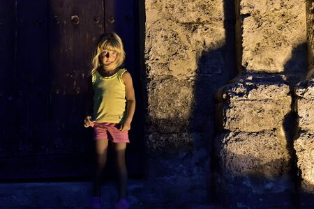 cuba girl: Night shot of little girl leaning against old building at street. Havanna Cuba Stock Photo