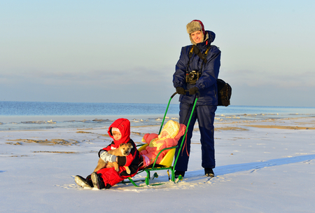 beauties: RUSSIA, COAST OF LADOGA LAKE - NOVEMBER 29, 2014: In sunny winter day beautiful young mother walks with two little daughters on the coast of the frozen Ladoga Lake