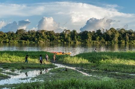 Nuova Guinea: Nuova Guinea, Indonesia - 26 giugno: bambini sconosciuti giocano sulla riva del fiume, nei pressi del villaggio. Tramonto, fine della giornata. 26 giugno 2012 nel villaggio, Nuova Guinea, Indonesia