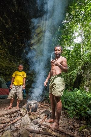 new guinea: NORD-OVEST Irian Jaya, Nuova Guinea, Indonesia-gennaio 12, 2009: La gente del posto dell'isola della Nuova Guinea ha fatto fuoco per cuocere il cibo. Persone provenienti da una tribù di JAFI, (JAFI Wagarindem, Wargarindem, Warlef, Yaffi, Zorop) Editoriali