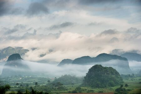 pinar: Peaceful view of Vinales valley at sunrise. Aerial View of the Vinales Valley in Cuba. Morning twilight and fog. Fog at dawn in the Valley of Vinales in Pinar del Rio, famous for tobacco plantations
