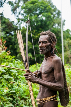ancient warrior: NDONESIA, NEW GUINEA, IRIAN JAYA, ONNI VILLAGE - JUNE 27, 2012: The Papuan from a Korowai tribe. Korowai kombai (Kolufo) with bow and arrows on the natural forest background Editorial