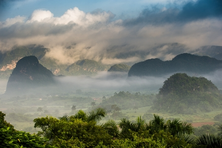 pinar: Aerial View across the Vinales Valley in Cuba. Morning twilight and fog. Fog at dawn in the Valley of Vinales in Pinar del Rio, famous for tobacco plantations in Cuba Stock Photo