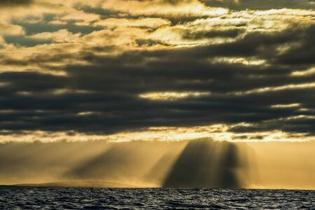 crepuscular: Crepuscular sun rays during sunset over the sea. Sea landscape. An morning, Clouds sky and mountains. False bay. South Africa. Stock Photo
