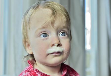 tomando leche: Cierre de la diversión retrato de la niña linda con bigotes de leche. Retrato de una niña feliz con el yogur en la cara. Foto de archivo