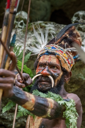 Nuova Guinea: Nuova Guinea, Indonesia - 2 FEBBRAIO: Il guerriero di una trib� di Papua di Yafi in abiti tradizionali, ornamenti e colorazione. Obiettivi per spara un arciere. Nuova Guinea, Indonesia. 2 Febbraio 2009. Editoriali