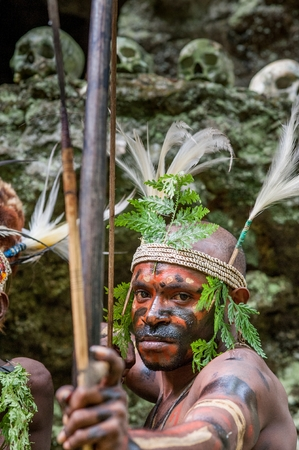 Nuova Guinea: NEW GUINEA, INDONESIA - 2 FEBRUARY: The warrior of a Papuan tribe of Yafi in traditional clothes, ornaments and coloring. Aims for shoots an archer. New Guinea Island, Indonesia. February 2, 2009. Editoriali