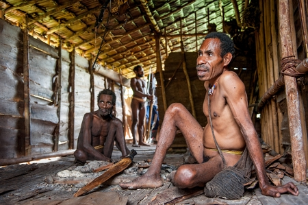 new guinea: ONNI VILLAGE, Nuova Guinea, Indonesia - 24 giugno: Il ritratto Korowai uomo in casa sull'albero. Korowai Kombai (Kolufo) .Al 24 Giugno 2012 a Onni Village, Nuova Guinea, Indonesia Editoriali