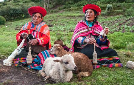 pisaq: CUZCO, PERU - CIRCA 2007: Women and Lamb. Peruvian women spinning yarn .The Peruvian women in traditional  clothes weave a yarn, sitting on a grass near sheep