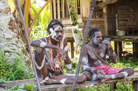 Nuova Guinea: JOW VILLAGE, ASMAT PROVINCE, IRIAN JAYA, INDONESIA- JUNE 28: The Asmat warrior in traditional dress sits on a wooden scaffold. On June 28, 2012 in Jow Village, Asmat province, New Guinea, Indonesia