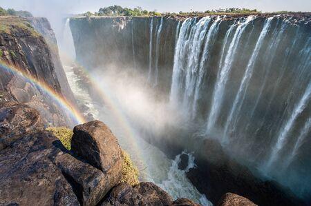 Rainbow over Victoria Falls on Zambezi River, border of Zambia and Zimbabwe. Africa