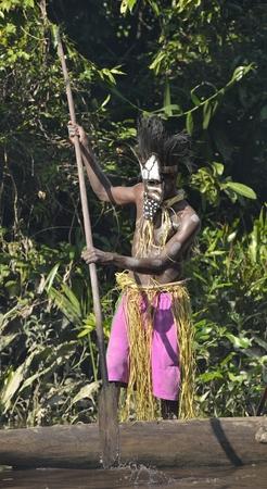 new guinea: YOUW VILLAGE, ASMAT REGIONE, Nuova Guinea, Indonesia - 23 maggio, 2016: Canoa cerimonia guerra di Asmat persone. Headhunter di una tribù di Asmat in una maschera con un remo. Nuova Guinea, Indonesia. 23 maggio 2016