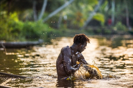 australasian: YOUW VILLAGE, ATSY DISTRICT, ASMAT REGION, IRIAN JAYA, NEW GUINEA, INDONESIA - MAY 23, 2016:  Asmat man is bathing in the river and wash away a body paint after the traditional ceremony of his tribe