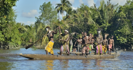 nuova guinea: INDONESIA, IRIAN JAYA, ASMAT PROVINCE, JOW VILLAGE - JUNE 23: Canoe war ceremony of Asmat people. Headhunters of a tribe of Asmat . New Guinea Island, Indonesia. June 23, 2016