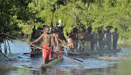 paddles: INDONESIA, IRIAN JAYA, ASMAT PROVINCE, JOW VILLAGE - JUNE 23: Canoe war ceremony of Asmat people. Headhunters of a tribe of Asmat . New Guinea Island, Indonesia. June 23, 2016
