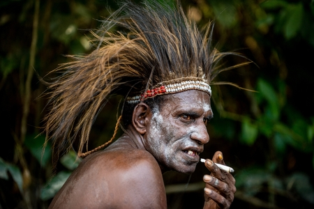 YOUW VILLAGE, ATSY DISTRICT, ASMAT REGION, IRIAN JAYA, NEW GUINEA, INDONESIA - MAY 23, 2016: Smoking man from the tribe of Asmat people. The Asmat Papua Welcoming ceremony. New Guinea.May 23, 2016 Editorial