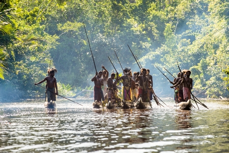 INDONESIA, IRIAN JAYA, ASMAT PROVINCE, JOW VILLAGE - JUNE 23: Canoe war ceremony of Asmat people. Headhunters of a tribe of Asmat . New Guinea Island, Indonesia. June 23, 2016