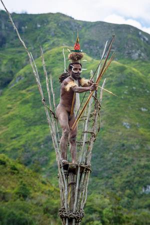DANI VILLAGE, WAMENA, IRIAN JAYA, NEW GUINEA, INDONESIA, 4 JUNE 2016: The Warrior of Dani tribe on the observation tower. July 2016 The Baliem Valley, Indonesian, New Guinea