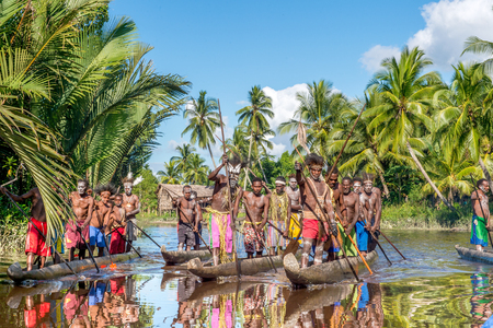 INDONESIA, IRIAN JAYA, ASMAT PROVINCE, JOW VILLAGE - JUNE 13: Canoe arriving during canoe war feast. Canoe war ceremony of Asmat people. Headhunters of a tribe of Asmat . New Guinea Island, Indonesia. June 13, 2016
