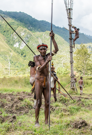 DANI VILLAGE, WAMENA, IRIAN JAYA, NEW GUINEA, INDONESIA - JUNE 4: The   armed Papuan. Warrior of Dani Dugum tribe with spear. June 4, 2016, New Guinea Island.