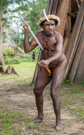 DANI VILLAGE, WAMENA, IRIAN JAYA, NEW GUINEA, INDONESIA - JUNE 4: The  armed Papuan Warrior of Dani Dugum tribe with spear. June 4, 2016, New Guinea Island.