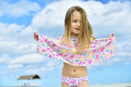 Cute little girl on a sandy beach. Blue sky background. Cuba. Caya Coco. Banque d'images