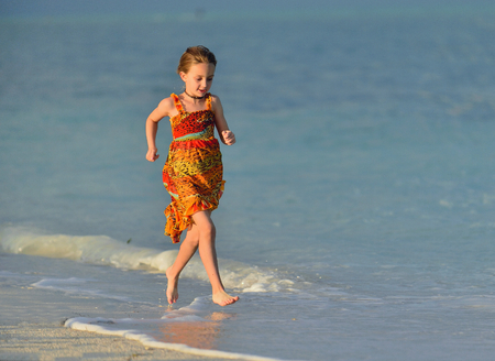Cute little girl running on beach in sunset light. Cuba.