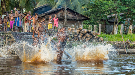 YOUW VILLAGE, ATSY DISTRICT, ASMAT REGION, IRIAN JAYA, NEW GUINEA, INDONESIA - MAY 23, 2016: Noisy fun kids. Children of the tribe of Asmat people bathe and swim in the river. New Guinea.May 23, 2016