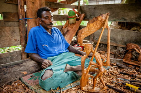 JOW VILLAGE, ASMAT PROVINCE, NEW GUINEA, INDONESIA - JUNE 28: Man from the Asmat Tribe carving with a chisel a statue. Asmat man was making a wood carving. June 28, 2012 Jow Village, Asmat, Indonesia