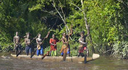 INDONESIA, IRIAN JAYA, ASMAT PROVINCE, JOW VILLAGE - MAY 23: Canoe war ceremony of Asmat people. Headhunters of a tribe of Asmat spear-oar in war paint. New Guinea Island, Indonesia. May 23, 2016