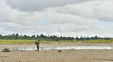 INDONESIA, IRIAN JAYA, COAST RIVER IN WILD JUNGLE NEW GUINEA - MAY 17: Woman from the tribe Korowai with baby on her back goes on the sandy shallows of the wild river. New Guinea, Indonesia. May 17, 2016 Editorial