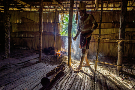 YOUW VILLAGE, ATSY DISTRICT, ASMAT REGION, IRIAN JAYA, NEW GUINEA, INDONESIA - MAY 23, 2016: Portrait of a man from the tribe of Asmat people with a drum in the men`s house. Asmat Welcoming ceremony.