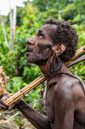 WILD JUNGLE OF NEW GUINEA ISLAND, INDONESIA - JUNE 24: Portrait of papuan man with bow and arrows from Korowai (Kolufo) tribe . June 24, 2012 near Onni Village, New Guinea, Indonesia