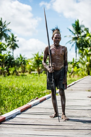 JOW VILLAGE IN JUNGLE, ASMAT DISTRICT, NEW GUINEA, INDONESIA - JUNE 14: Portrait of Headhunter of a Papuan Asmat tribe with spear. June 14, 2016, Asmat area, Irian Jaya province, Indonesia